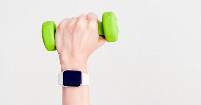 wrist wearing smart watch with hand holding dumbbell